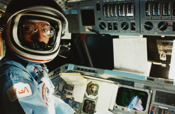 (Original Caption) Earth Orbit - Commander John W. Young of the Space Shuttle mission STS-9 is at the commander's station ready for the re-entry of the Space Shuttle Columbia.