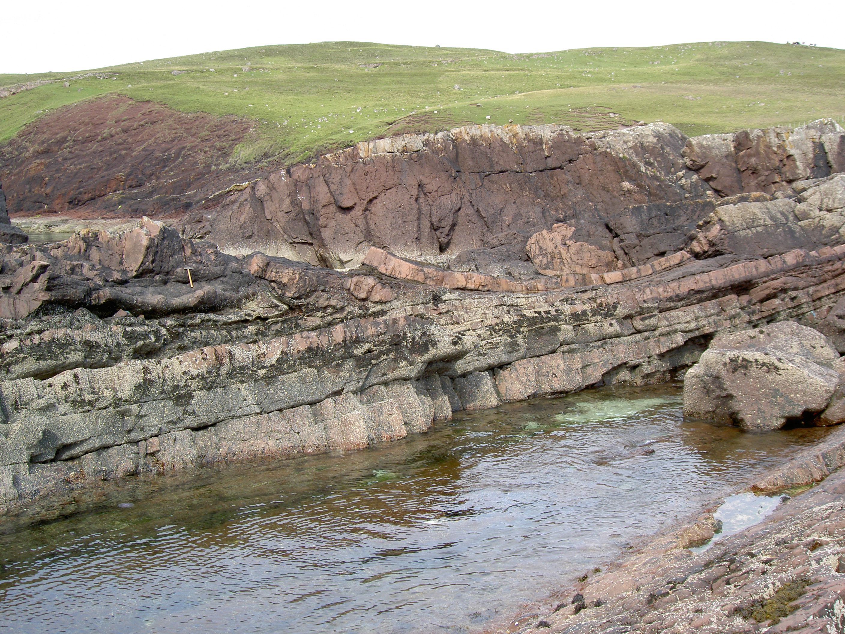 """A field photo take at Stoer showing the laminar beds of sandstone in the bottom of the picture. In the middle is the impact deposit (12m thick at this location) that contains """"rafts"""" of deformed pink sandstone."""