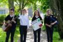 Picture by JASON HEDGES    Students at rural Speyside High School take break from classes to hold climate change protest in the hope that natural environment where they live will be preserved for future generations.  Picture: Fraser MacDonald (Guitar) Alexander Bond (white shirt)  Freya Gordon (protest sign) and Rhea Fraser (Bagpipes)