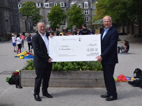 Bobby Anderson (Left) presenting chairman Graham Thom (Right) with cheque at Walker Road Primary school in Torry.