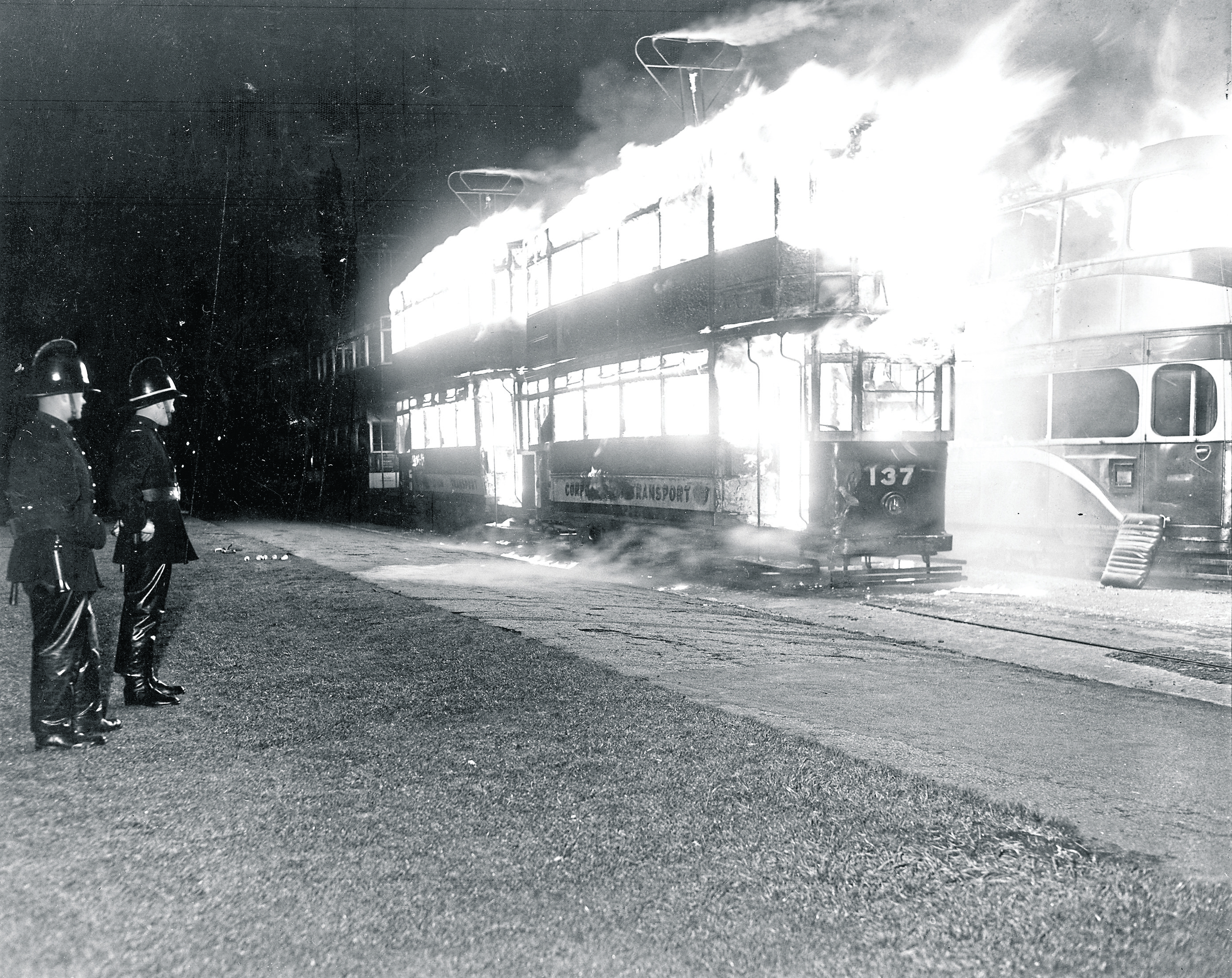 Firefighters on standby stand by and watch as the intense conflagration consumes the trams.