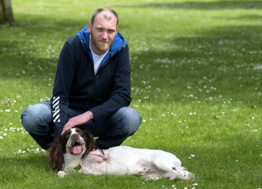 John Holt's dog lost a leg after falling down a hole. He blames the council for not filling it. Pictured is John with his dog Elmo. by Kath Flannerty