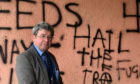 Councillor Iain Taylor highlighting the issue of vandalism as swastikas and pro IRA graffiti has been sprayed onto a wall in the Haughs, Turriff