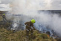 Firefighters tackles the wildfire which spread over a large area of deep peat at Killimster Moss.
