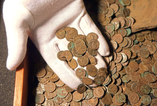 LONDON - NOVEMBER 19:  A man examines  Roman coins found in Snodland, Kent in the British Museum, on November 19, 2008 in London, England. The Roman coin hoard is one the most significant treasure finds of recent years and is being displayed to coincide with the announcement of the Treasure Annual Report.   (Photo by Oli Scarff/Getty Images)