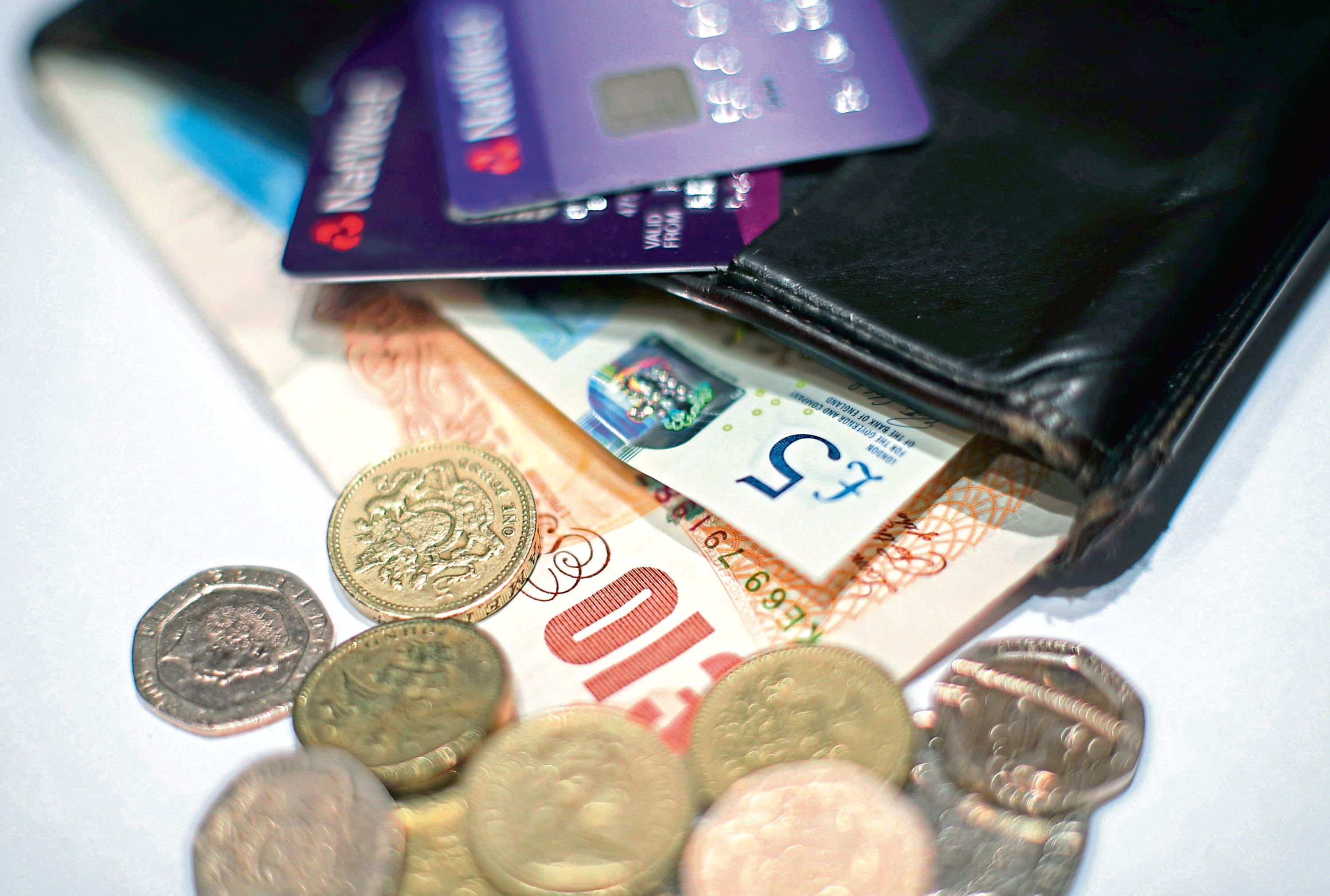 Coins and a five pound and ten pound banknotes and cards in a wallet.