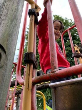 Under a watchful eye, Espen Grimshaw, aged two, is the only child his father has ever seen in Kinlochleven playpark, due to its poor state of repair.