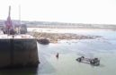 Vehicle recovery unit winching the van out of the water at Hopeman harbour in Moray.
