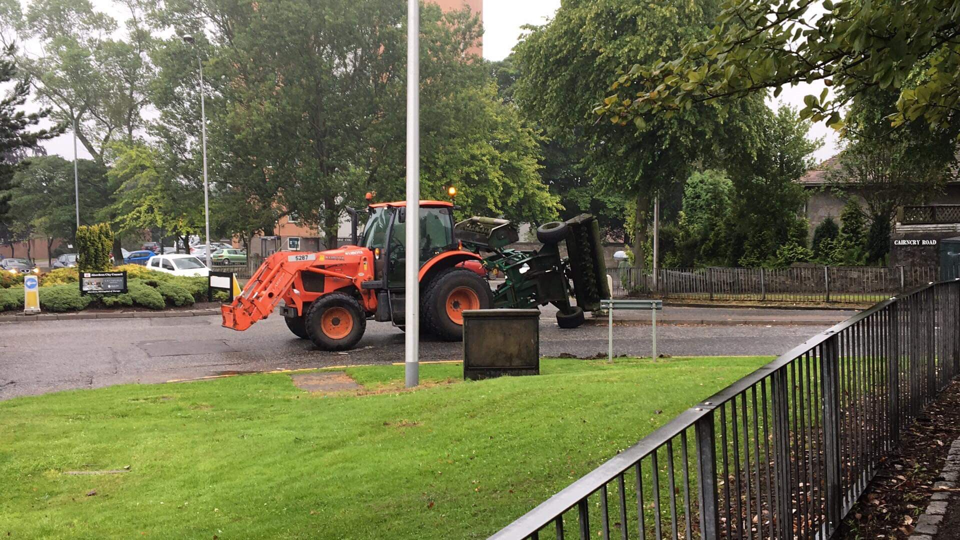 The tractor and its overturned grass cutter on Cairncry road.