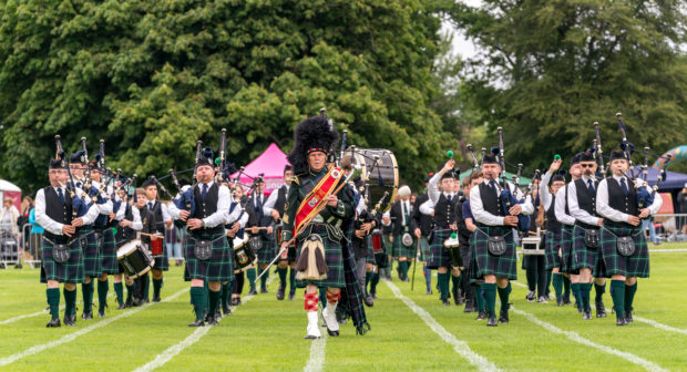 Forres and District Pipe Band enter the arena to commence the games.