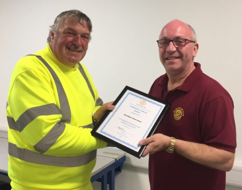 Gordon Lawrence is presented with his award by Scott Strachan of Ellon Rotary Club .
