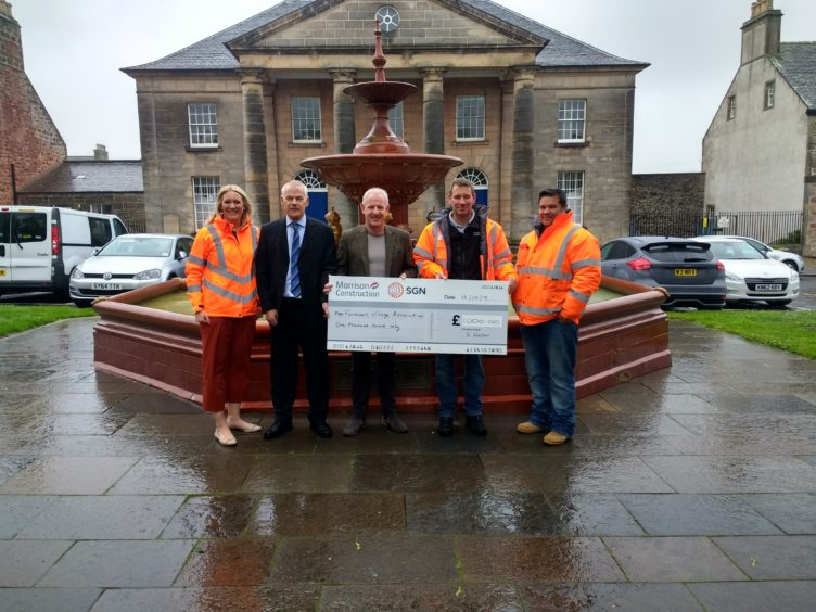 Morrison and SGN handing over the cheque.
