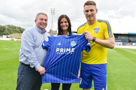 Prime Seafoods managing director George Forman and his daughter Naomi Charles present Peterhead FC captain Rory McAllister with the new home shirt.