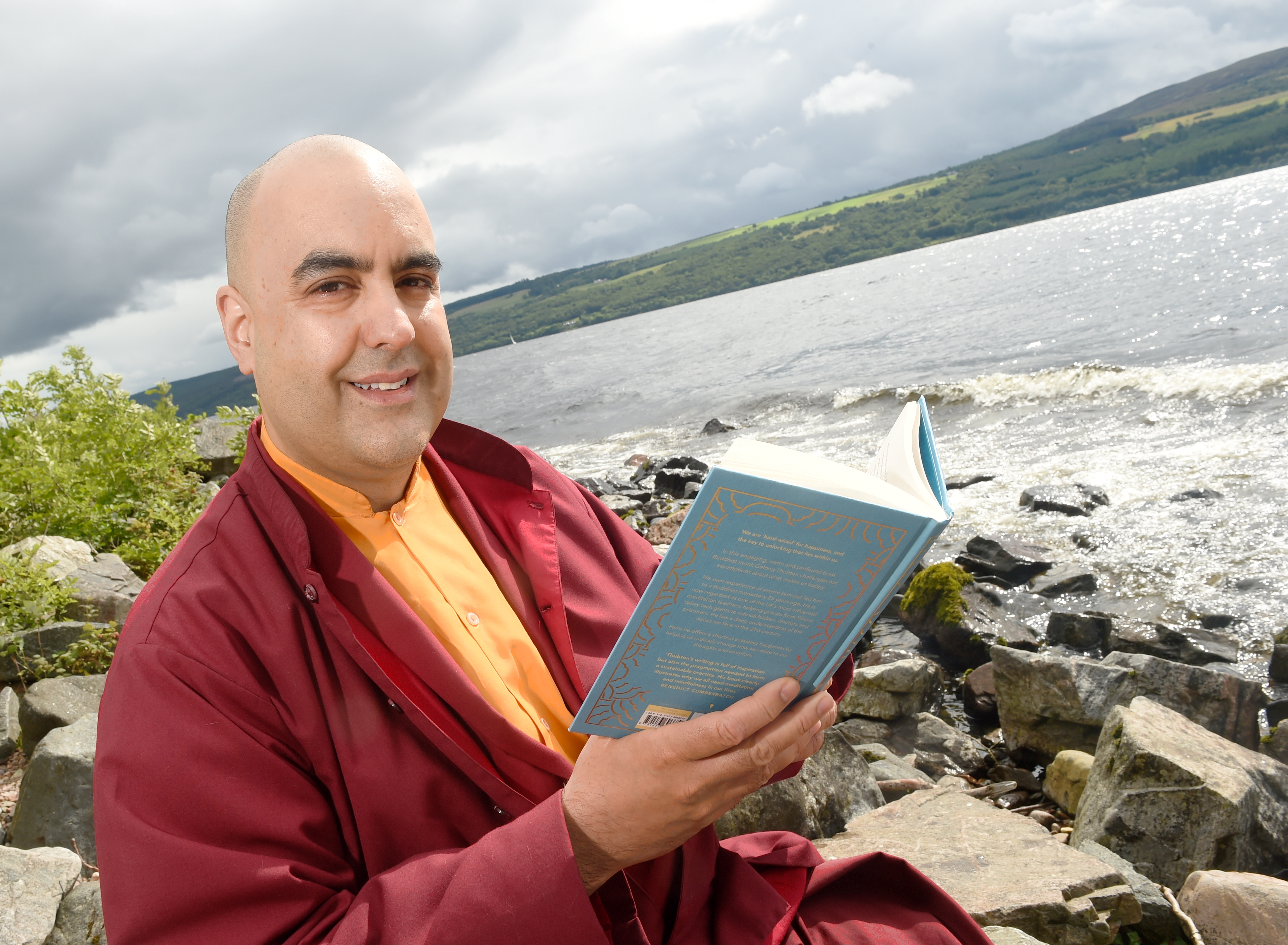 Author Gelong Thubten with his new memoir A Monk's Guide to Happiness on the shores of Loch Ness.
