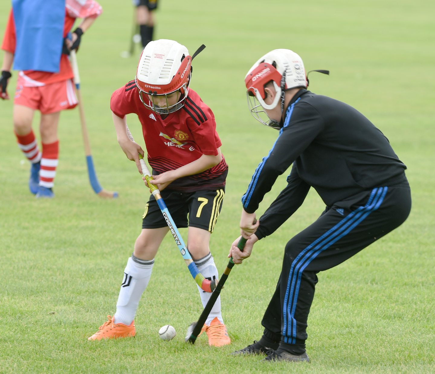 Youngsters battle over the ball during this Shinty exhibition. Picture by Sandy McCook