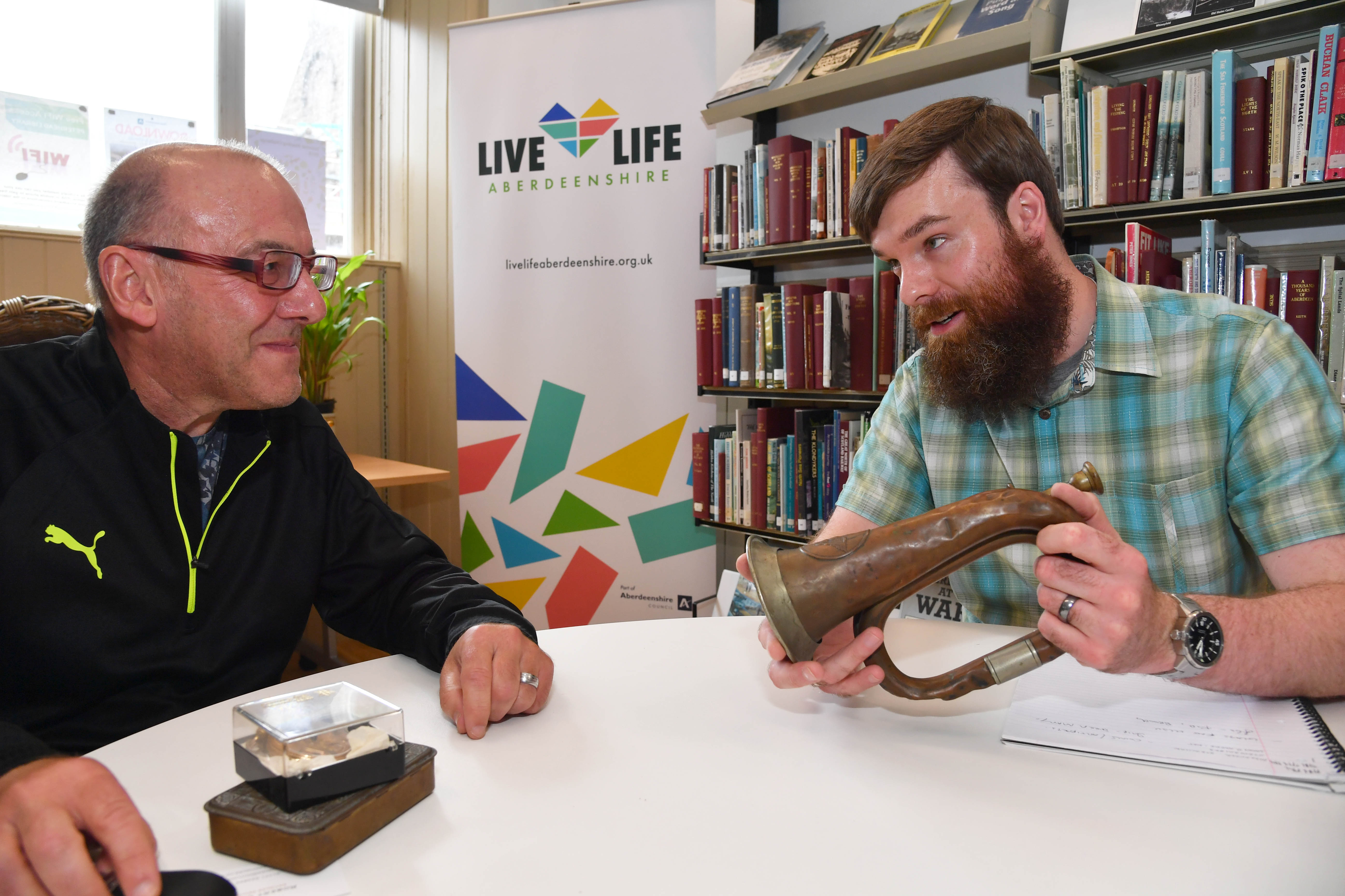 PETERHEAD SCOITTISH WEEK ROBERT COOK FROM ATTIC ANTIQUES EXAMINES A WORLD WAR 1 GERMAN SIGNAL HORN  BELONGING TO RICHARD FRASER WHOSE GREAT GRANDFATHER BROUGHT  IT HOME FROM THE TRENCHES.