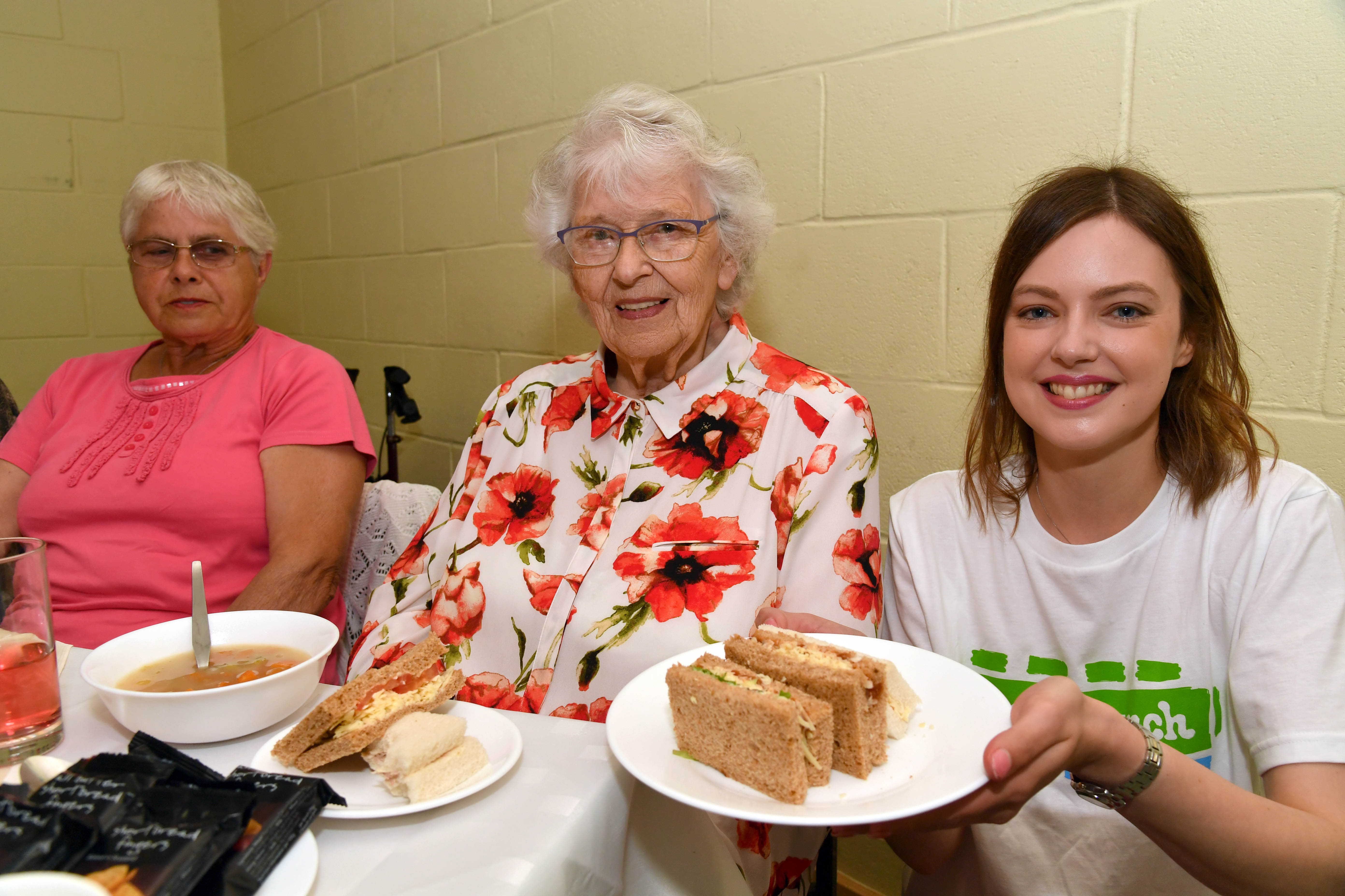 Tanita Addario serves up a plate of sandwiches with Frances Norrie (L) and Ellen Massie at the Big Lunch at the Mustard Seed cafe.