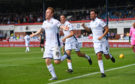 Dundee's Danny Johnson celebrates with teammates Shaun Byrne (R) and Cameron Kerr