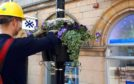 The power firm used lifting equipment to fit the new flower baskets.