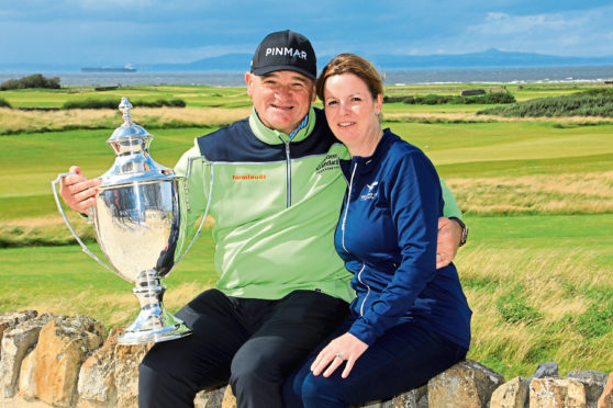 Paul Lawrie of Scotland and his wife Marian pose for a photograph after winning the Scottish Senior Open played at Craigielaw Golf Club.