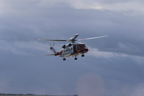 A Coastguard helicopter being used to help rescue a walker who had fallen down a cliff in Shetland.