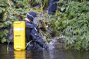 Officers with what is understood to be CCTV recording equipment by the Caledonian Canal.