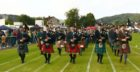 Parade of pipers including the gold and silver medals winners arrive on the games field after marching from Argyll Square in Oban.