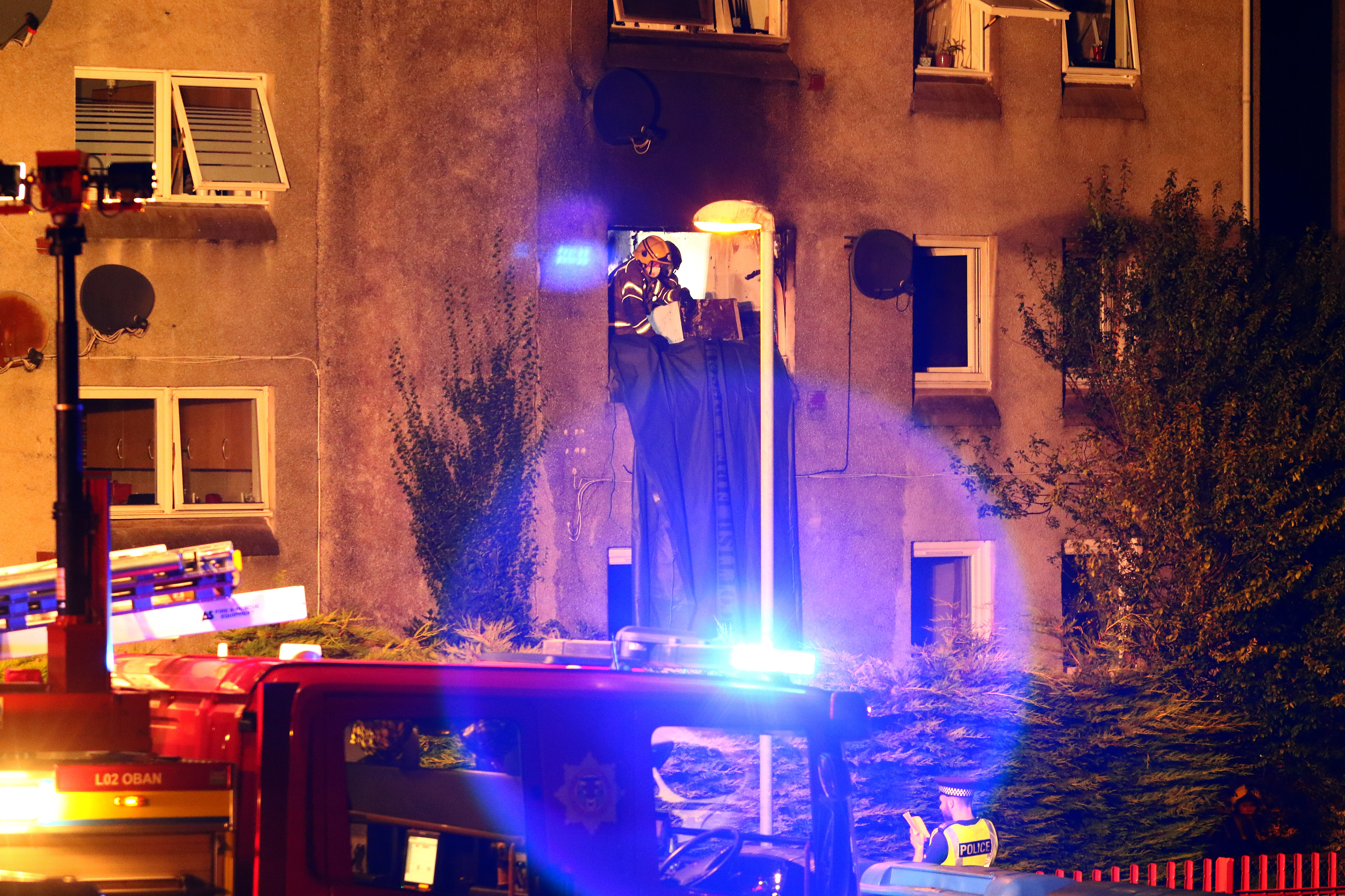 Fire crews from Fire Scotland remove fire damaged debris as Fire caused extensive damage to flats in colonsay terrace oban