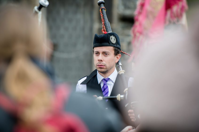 Piper Calum MacColl looks focused ahead of the march