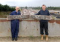Raymond Sharp and his son Doug Sharp with two original Kintore Railway Station signs.