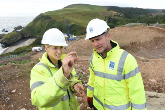 Cabinet Secretary for Transport, Infrastructure and Connectivity Michael Matheson and archaeologist Mary Peteranna thoroughly analyse one of the artefacts discovered. Picture by Sandy McCook