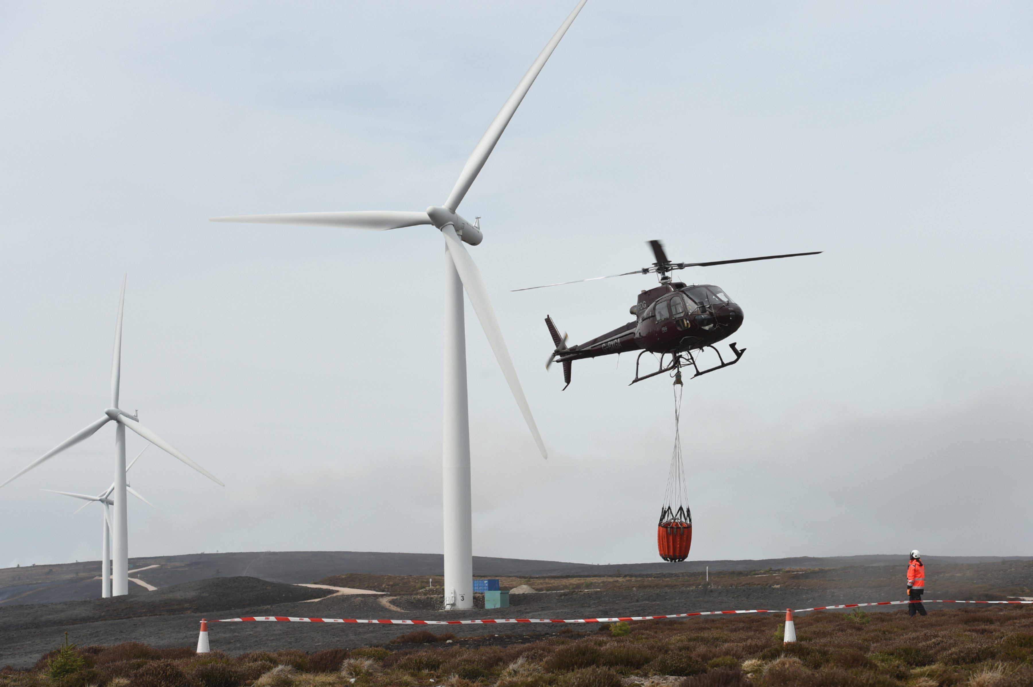 A helicopter assists at the scene of a wildfire at Paul's Hill Wind Farm near Knockando, Speyside.  Picture by Jason Hedges