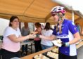 VOLUNTEER ERIN HAY SERVES UP SOUP AND SANDWICHES TO CYCLIST ALLISON MCKENZIE.