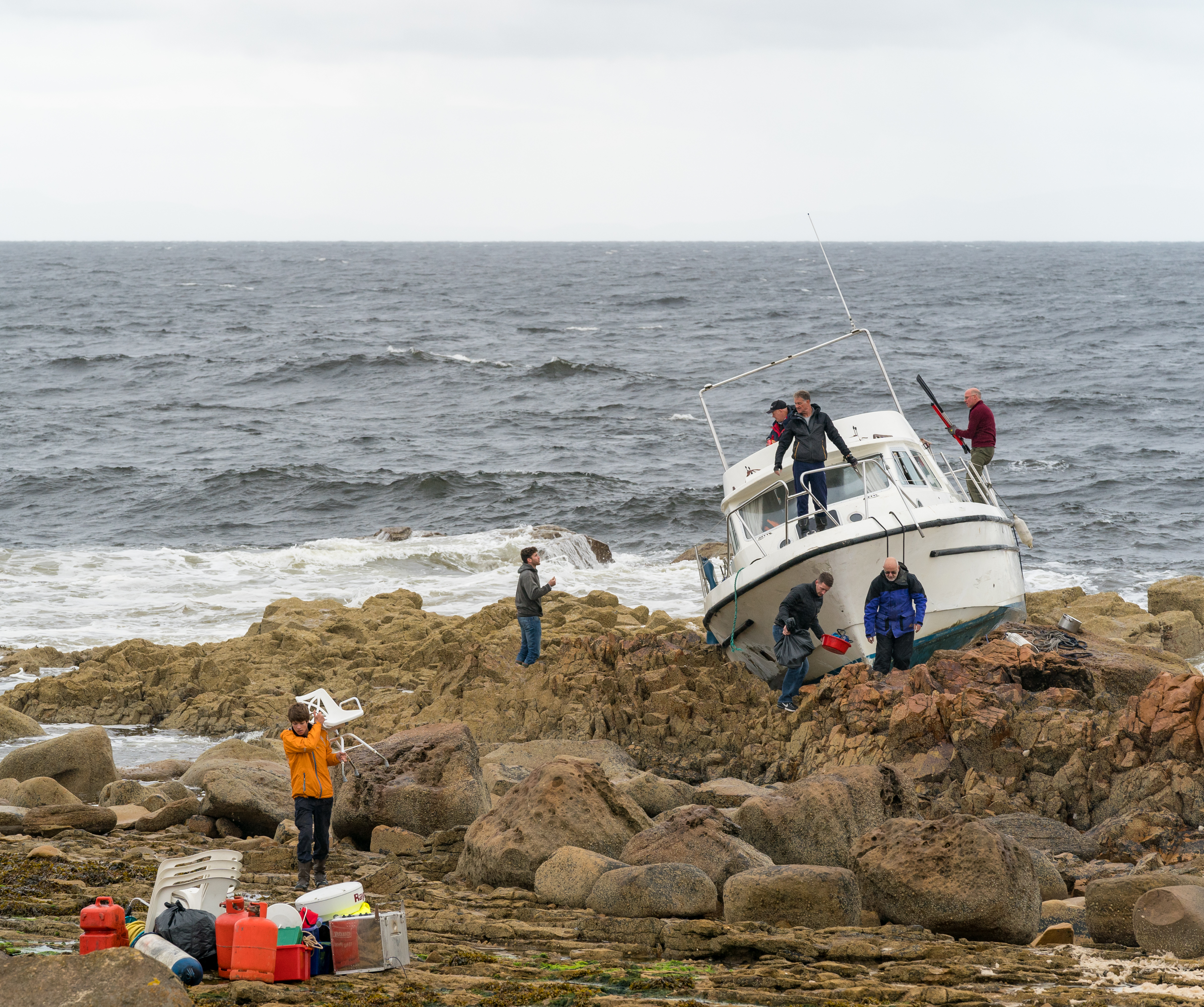Coastguard, boat owners and friends salvage equipment before the boat breaks up on the rocks