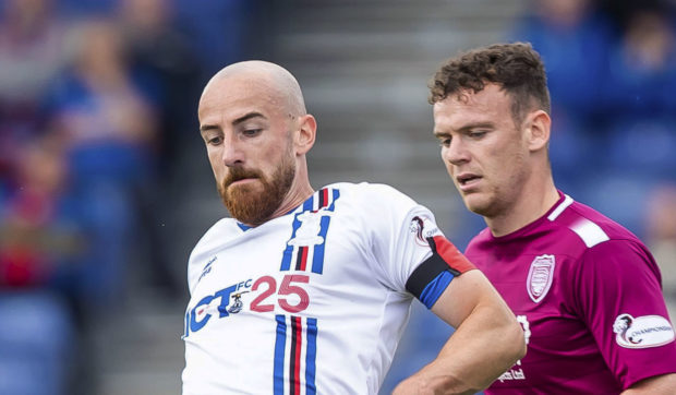 Inverness' James Vincent (L) in action with Arbroath's James Murphy.