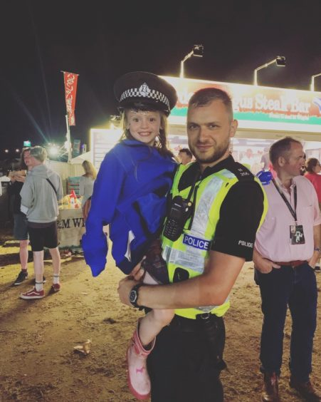 Mila Smillie, 5, from Inver, Tain at Belladrum trying on a policeman's hat.