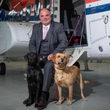 CHC's Europe, Middle East and Africa Regional Director Mark Abbey with Copter and Ellie, who are trained by the Veterans With Dogs charity.