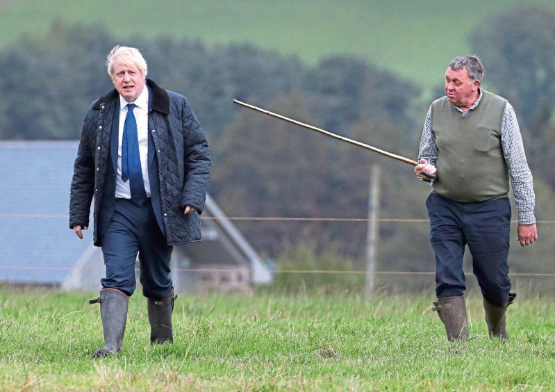 Pete Watson, right, shows Prime Minister Boris Johnson around his Darnford Farm.