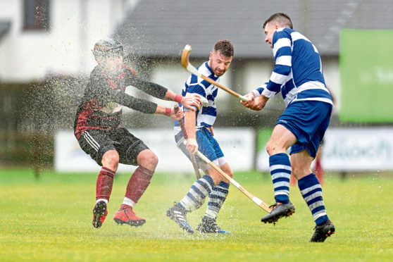 Malcolm Clark (Oban) with Drew and Steven MacDonald (both N'more). Tulloch Homes Camanachd Cup Final - Newtonmore v Oban Camanachd - played at An Aird, Fort William.