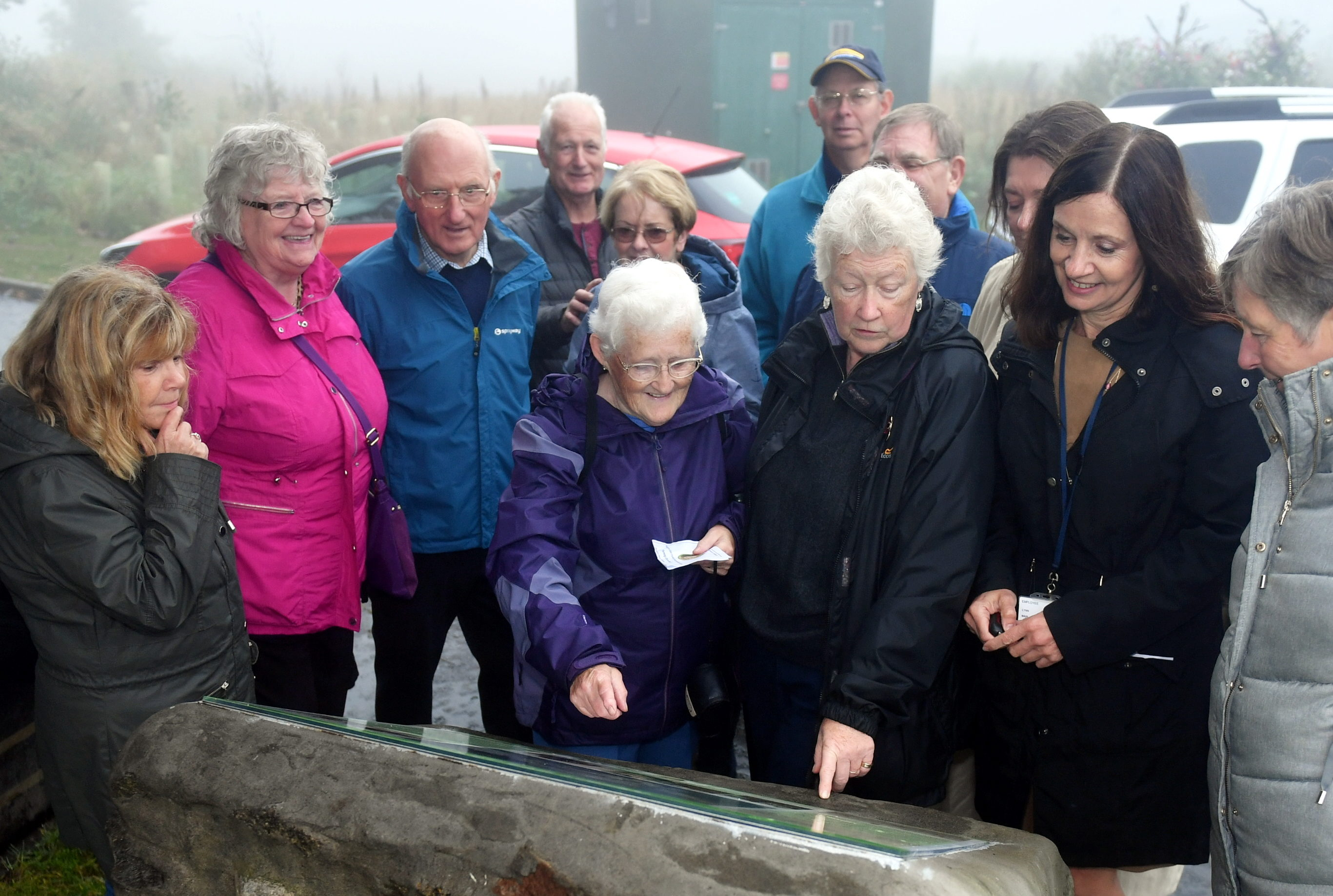 Liz Allen, centre, shows off the plaque to Cove residents.