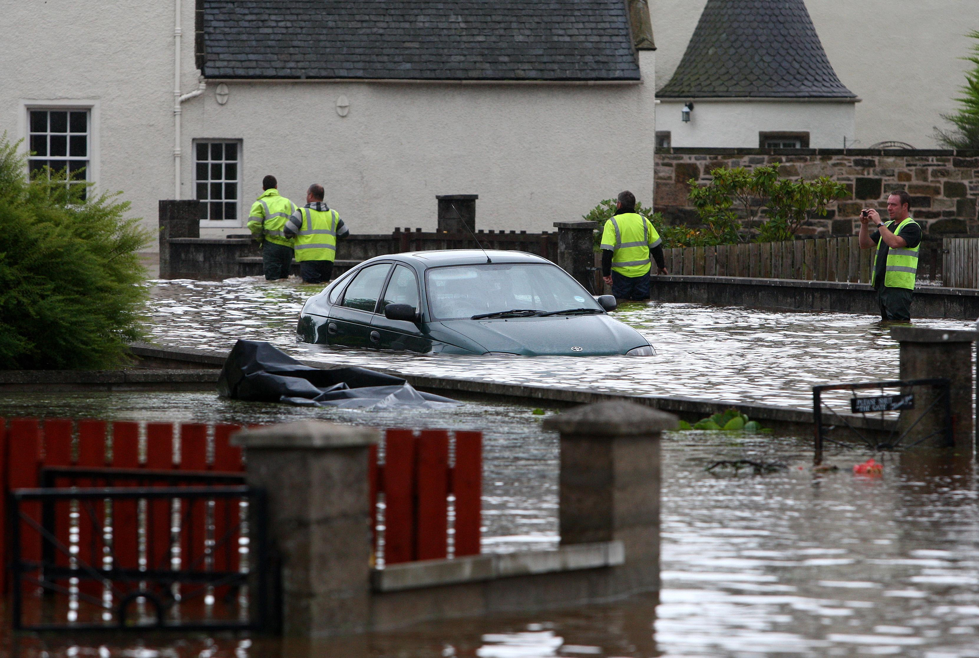 A car is submerged by flood water after the River Lossie burst in banks in Elgin.