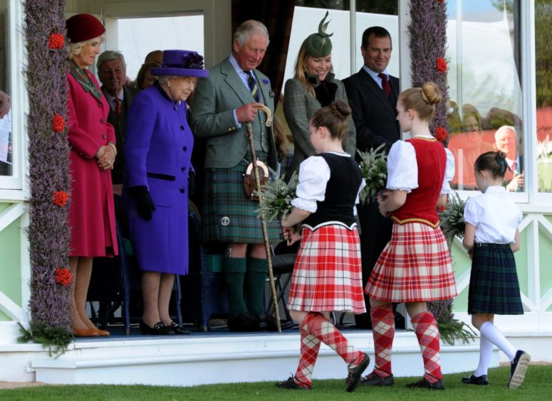 Picture of (L-R) Camilla Duchess of Rothesay, The Queen, Prince Charles and Mrs Autumn Phillips receiving flowers from (L-R) Amelia Fraser, 10, Kaitlin Frew, 11, Eilidh Murdoch, 7..  Picture by KENNY ELRICK