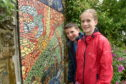 A new mosaic built with the help of pupils of Crown Primary School, Inverness was unveiled at the Highland Hospice. Here are Liam Buchan and Lucy McIntosh admiring their work. Picture by Sandy McCook