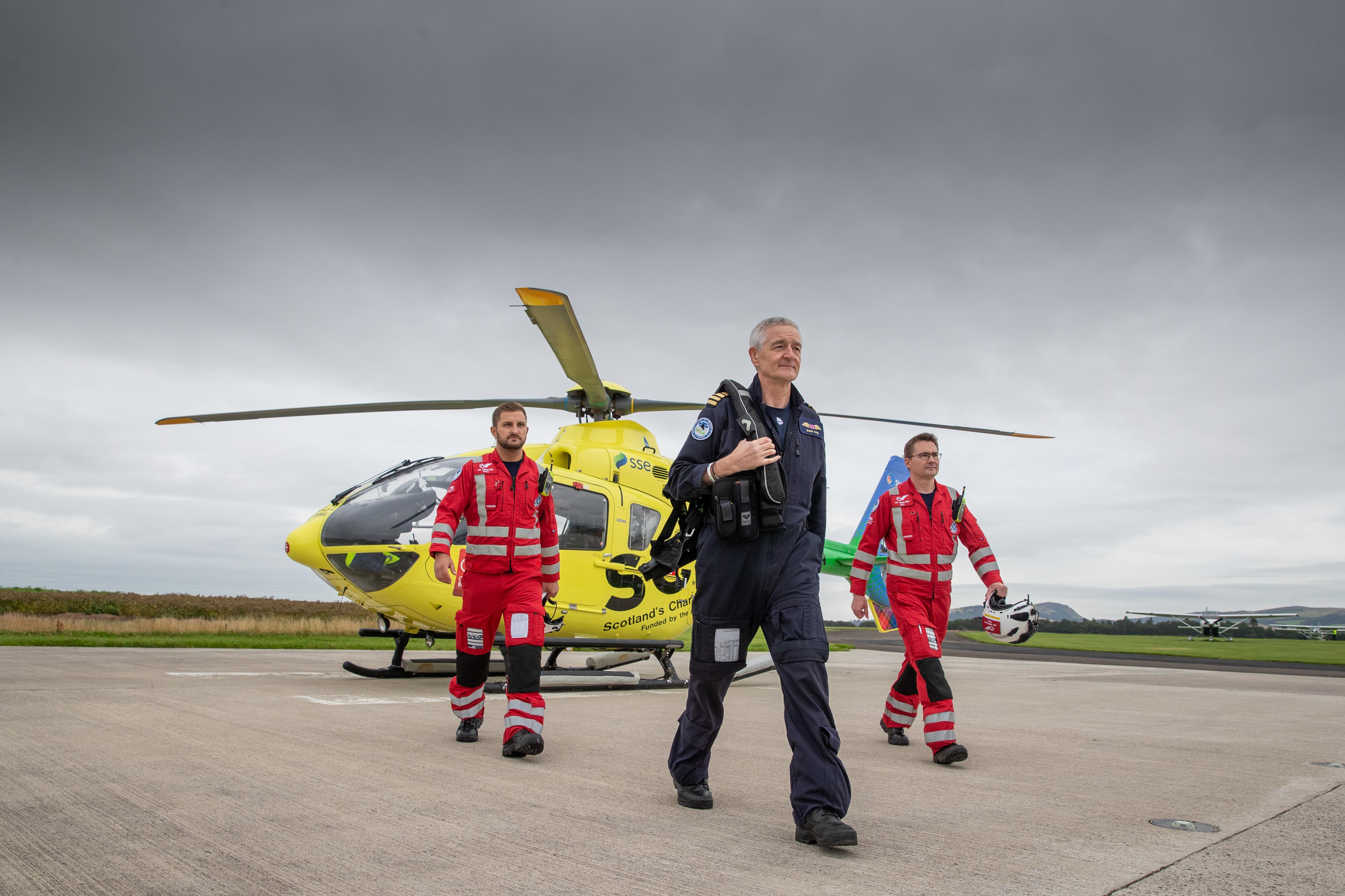 Pilot Shaun Rose and paramedics Darren O'Brien (L) and Matt Allen alongside the SCAA Helicopter