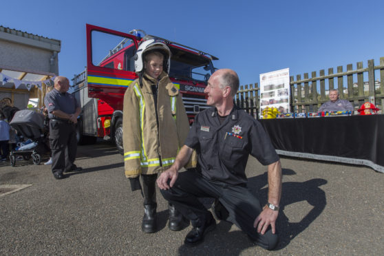 Wick Community Fire Station's acting watch manager Hugo Ross with seven year old Scott Allan