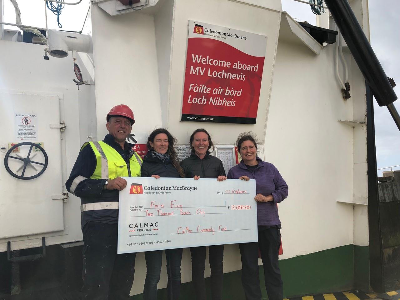 V Loch Nevis crewman Murdo Ferguson presents the Community Fund cheque to representatives of Fèis Eige.