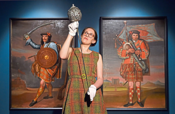 William Grant Foundation Research Fellow Dr Rosie Waine, one of the curators of the exhibition Wild and Majestic: Romantic Visions of Scotland, holds a sword which belonged to Bonnie Prince Charlie in front of a pair of portraits depicting two members of the household of the Chief of Clan Grant (paintings by Richard Waitt, 1714).