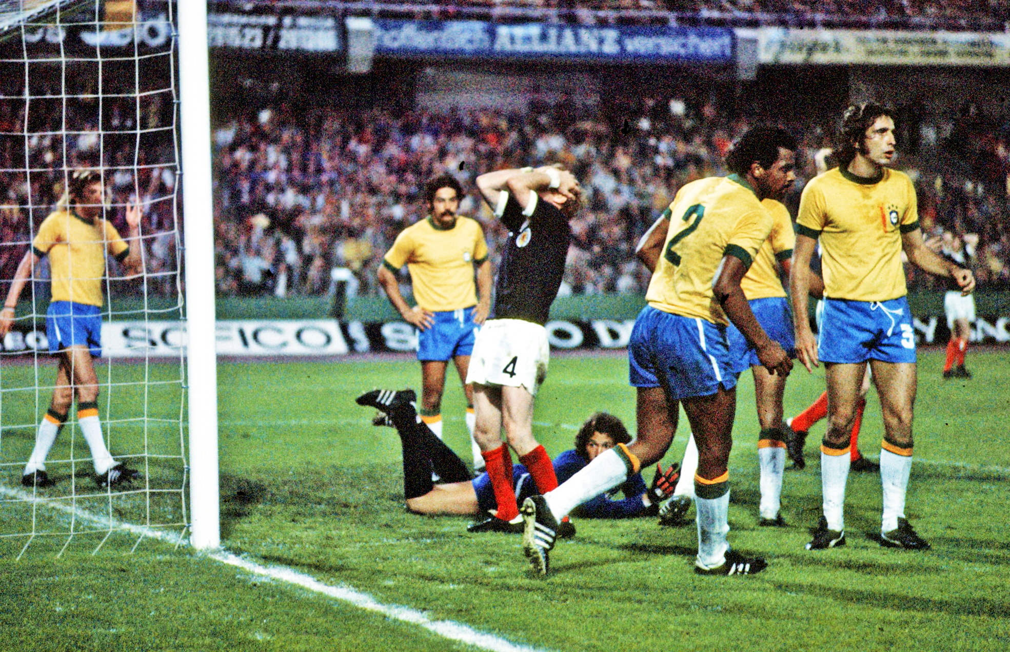 World Cup 1974: Scotland's skipper Billy Bremner (left) holds his head after he had beaten the Brazil keeper Leao (grounded) to the ball and then put the ball past the post, from inside the six yard box.