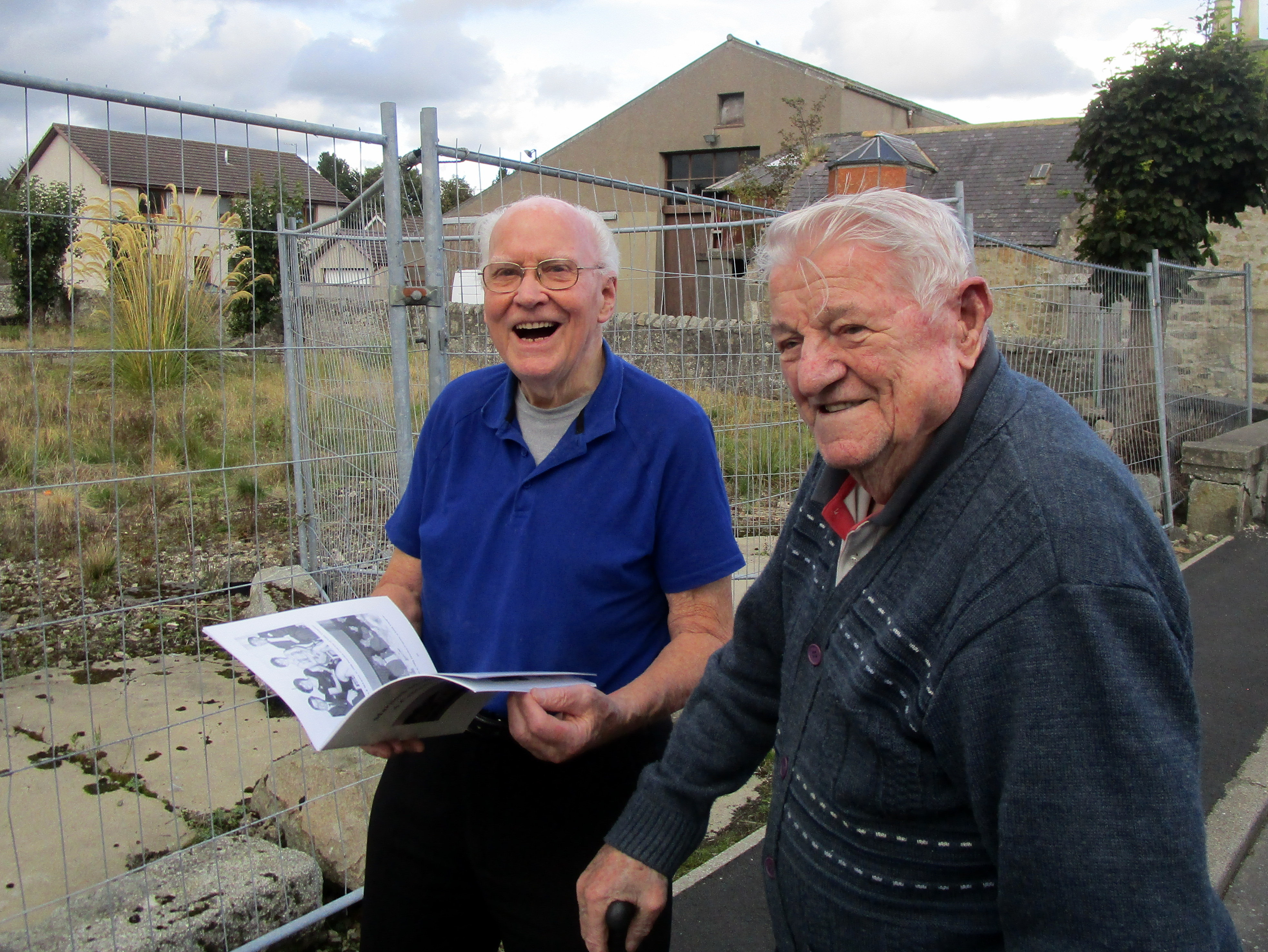 Hugh Youngson, 88, and Charlie Anderson ,91, who grandfathers built the hall, getting a preview of the book in front of the site of the former Marnoch Memorial Hall