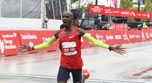 Mo Farah of Great Britain, raises his arm after he finishes in first place during the Bank of America Chicago Marathon, Sunday, Oct. 7, 2018, in Chicago. (AP Photo/Matt Marton)